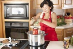 mujer con delantal rojo cocinando con olla express