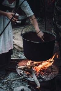 mujer cocinando con un horno holandés de color negro