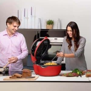 una pareja cocinando con una gran freidora Klarstein roja